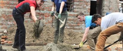Volunteers in Nepal dig up sand for cement to help rebuild schools as part of their construction volunteer project.